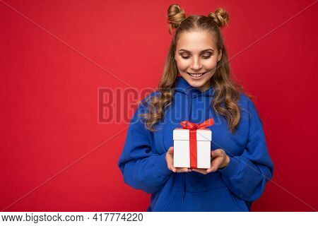 Shot Of Attractive Happy Smiling Young Blonde Woman Isolated Over Red Background Wall Wearing Blue T
