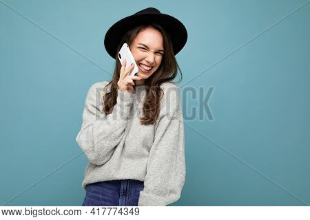 Attractive Young Smiling Laughing Woman Wearing Black Hat And Grey Sweater Holding Smartphone Lookin