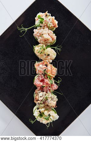 Cucumber wrapped sushi - Gunkan Maki Sushi with Seafood and sliced cucumber wrap around. Delicious Gunkan Sushi on black slate plate. Isolated on white background. Top view