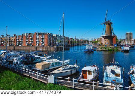 View of the harbour of Delfshaven and the old grain mill De Destilleerketel. Rotterdam, Netherlands