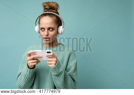Closeup Photo Of Beautiful Sad Young Woman Wearing Blue Sweater Isolated Over Blue Background Wearin