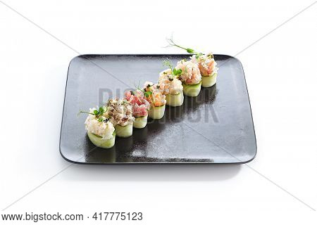 Cucumber wrapped sushi - Gunkan Maki Sushi with Seafood and sliced cucumber wrap around. Delicious Gunkan Sushi on black slate plate. Isolated on white background