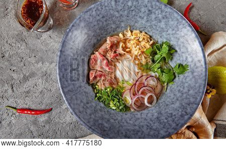 Vietnamese Cuisine - Beef Pho Noodle Soup or Pho Bo Soup. Served with Fresh Greens in Blue Bowl on Textured Dark Gray Table. Pho Bo Soup with Spicy Sauces. Top View