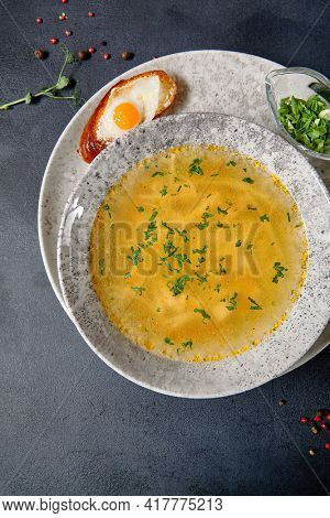 Traditional Bowl Food - Chicken Noodle Soup on Dark Table. Soup in ceramic bowl on dark textured background with food ingredients