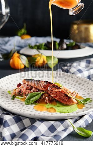 Fish Plate Restaurant Food - Grilled Salmon Steak with Vegetables Tartare. Salmon Fillet Garnished with Pesto and Citrus Sauce and Basil Leaf. Table with Kitchen Towel. Pouring Orange Sauce in Plate