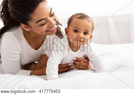 Joyful African Mommy Playing With Toddler Baby On Bed Indoor