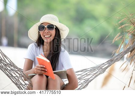 Lifestyle Young Woman Using Laptop Working And Reading Book For Relax On The Beach. Asian Smiling P