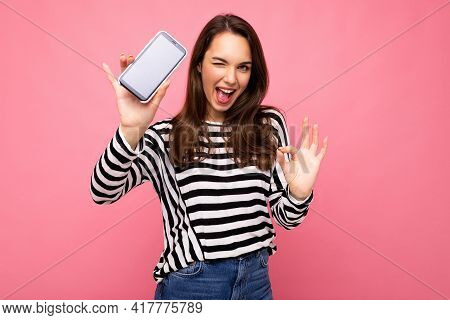 Winking Beautiful Happy Young Woman Wearing Striped Sweater Isolated Over Background With Copy Space