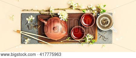 Asian Tea set on stone slate board, ceramic teapot, cups, dried tea and spring branches, tea ceremony banner, flat lay