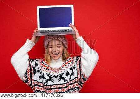 Photo Shot Of Beautiful Smiling Blonde Young Woman Holding Computer Laptop With Empty Monitor Screen
