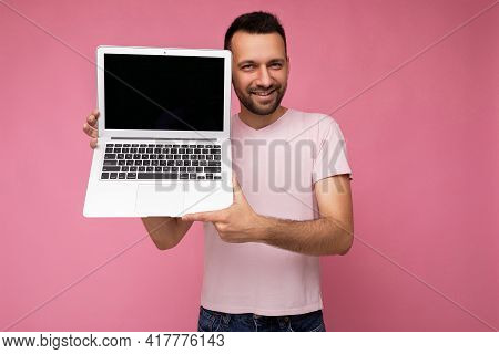 Handsome Smiling Man Holding Laptop Computer Looking At Camera In T-shirt On Isolated Pink Backgroun