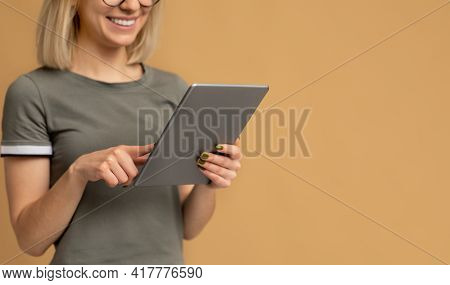 Unrecognizable Young Woman With Newest Digital Tablet Standing On Beige Studio Background With Empty