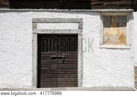 Canza (vco), Italy - June 21, 2020: An Old Wooden Door And A Religius Paint At Canza Village, Formaz