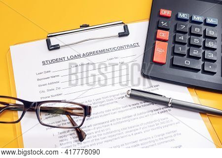 Blank Student Loan Application, Calculator, Pen And Eyeglasses On Table. Education Cost Concept