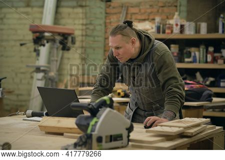 Concentrated Adult Craftsman Checking Information On Laptop While Working In Carpentry Workshop. Pro