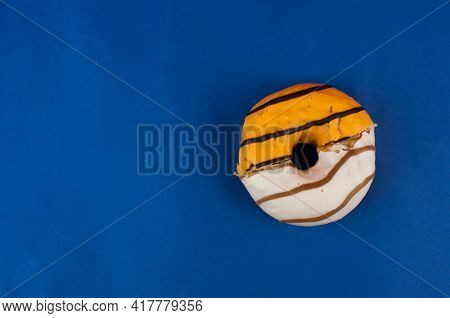 Half the donut is eaten. Two halves of the donut in one. Whole donut made up of two halves. Top view