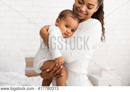 African Mommy Hugging Baby Son Carrying Him In Arms Indoors