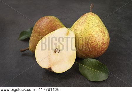 Two Whole And Half Organic Fresh Juicy Sweet Pears. Pears With Foliage On A Gray Cement Table. Healt