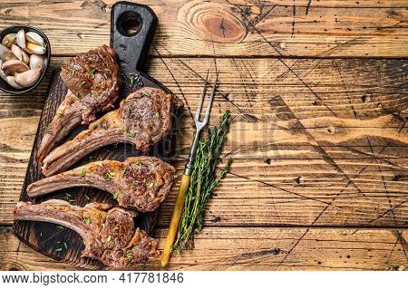 Grilled Lamb Mutton Meat Chops Steaks On A Cutting Board. Wooden Background. Top View. Copy Space
