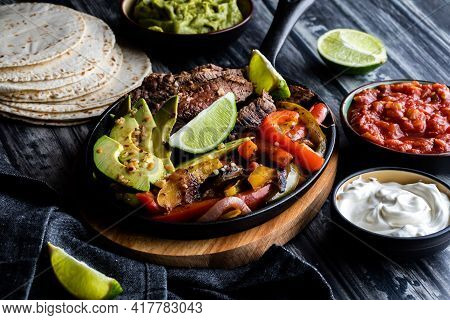 Close Up Of A Skillet Filled With Steak, Peppers And Avocados To Make Fajitas, Surrounded By Other T