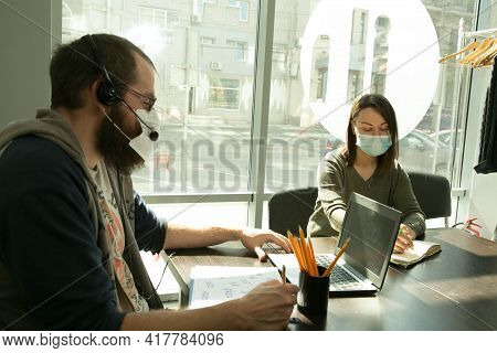 An Online Lesson During Quarantine. Young Teachersin Medical Masks Conduct An Online Lesson.