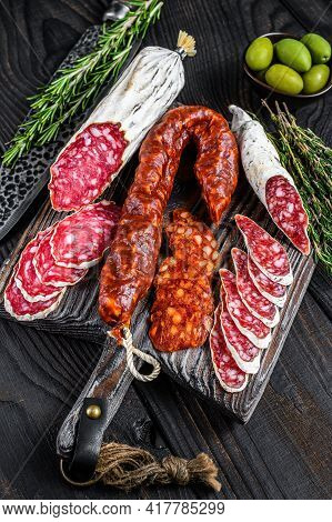 Spanish Tapas Sliced Sausages Salami, Fuet And Chorizo On A Wooden Cutting Board. Black Wooden Backg