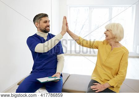 Senior Woman Patient Give Five To Her Male Physiotherapist After Successful Treatment At A Wellness