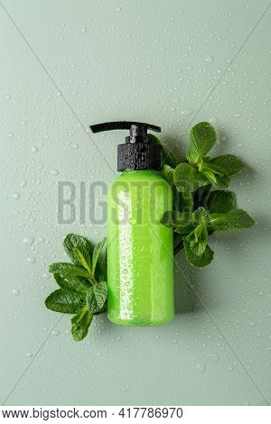 Green Cosmetic Bottle With Dispenser, Fresh Mint And Water Drops. Organic Cosmetics Concept. Cosmeti