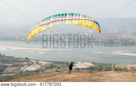 Paragliding In The Sky. Paraglider  Flying Over Landscape From Beautiful View Mekong River At Wat Ph