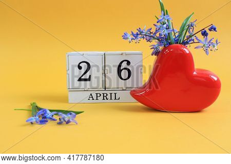 Calendar For April 26: A Bouquet In A Heart-shaped Vase With Blue Flowers And Numbers On Cubes 26, T