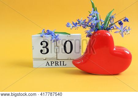 Calendar For April 30: A Bouquet In A Heart-shaped Vase With Blue Flowers And Numbers On 30 Cubes, T