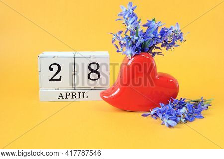 Calendar For April 28: A Bouquet In A Heart-shaped Vase With Blue Flowers And Numbers On Cubes 28, T