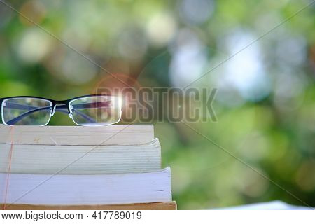Education Learning Concept With Open Book Or Textbook In Library, Stack Piles Of Book On Table And S