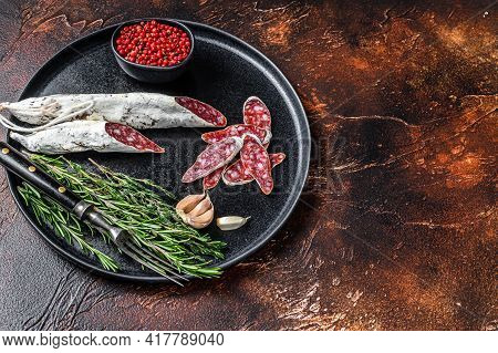 Charcuterie With Fuet Salami Sausage And Rosemary On A Plate. Dark Background. Top View. Copy Space