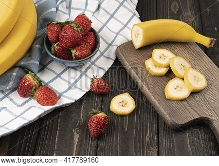 Sliced Yellow Ripe Bananas On Wooden Desk, With Fresh Ripe Strawberries In A Blue Glaze Bowl, Rustic