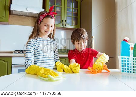 Positive Children Makes Cleaning The Kitchen Table. Smiling Boy And Girl Rub The Dust In The House.