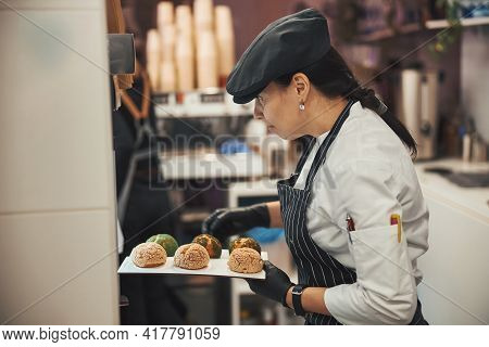 Qualified Confectioner Taking Freshly-baked Dessert Scones Out Of Oven