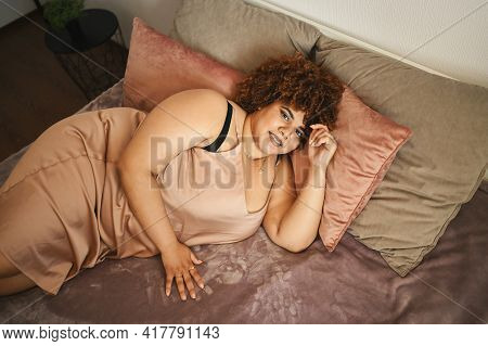 Beautiful Curvy Plus Size African Black Woman Afro Hair Lying On Bed In Silk Powder Pink Dress Cozy