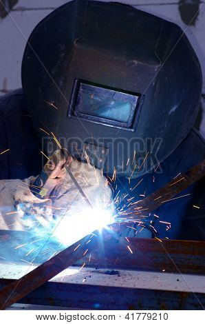 welder worker welding metal. Bright electric arc and sparks