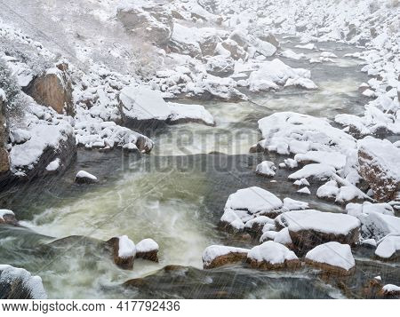 rapids on a mountain river in heavy spring snowstorm - Poudre River in northern Colorado