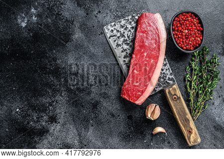 Fresh Raw Top Sirloin Beef Meat Steak On A Butcher Cleaver. Dark Wooden Background. Top View. Copy S
