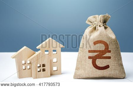 Ukraine Hryvnia Money Bag And Residential Buildings. City Municipal Budget. Mortgage Loan. Purchase
