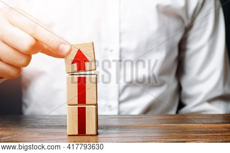 Man Collects A Tower Of Blocks With An Arrow. Step-by-step Career Growth. Concept Of Development To