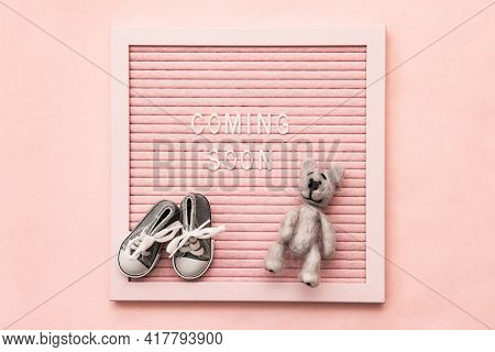 Waiting For Labour, Maternity Concept. Coming Soon Words On Pink Frame With Baby Shoes And Teddy Bea