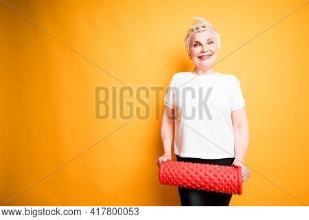 Cheerful Adult Woman Holding Fascia In Her Hands Smiling. Isolated On Yellow Background