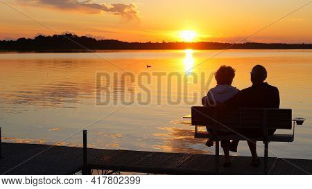 Silhouette Of Two People On A Bench On A Dock As They Enjoy A Sunset Over A Beautiful Lake In Minnes