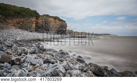 South Wales Coastline, Showing The Water Lapping Against The Rocky Shore, Flanked By High Cliff.  Th