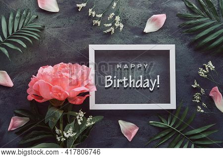 Happy Birthday Card With Peony And Palm Leaves. Flowers, Petals And Exotic Leaves Around White Frame
