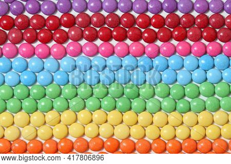 Colorful And Sweet Smarties Background. Chocolate Buttons In Lines And Colors Of Rainbow.