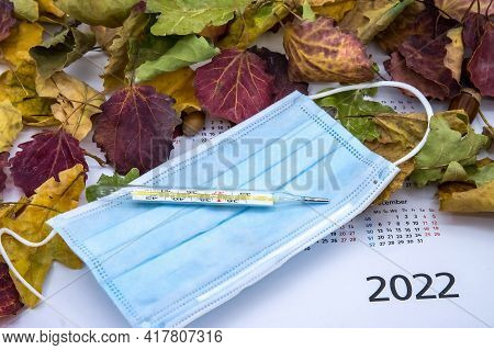 Medical Mask And Thermometer. Autumn Leaves And Thermometer.seasonal Morbidity In The Population In